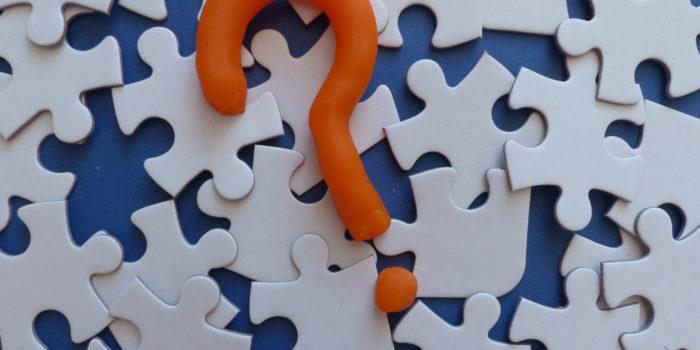 Losse puzzelstukjes met een oranje vraagteken er bovenop. als symbool voor de coaching die Saisi aan biedt.
