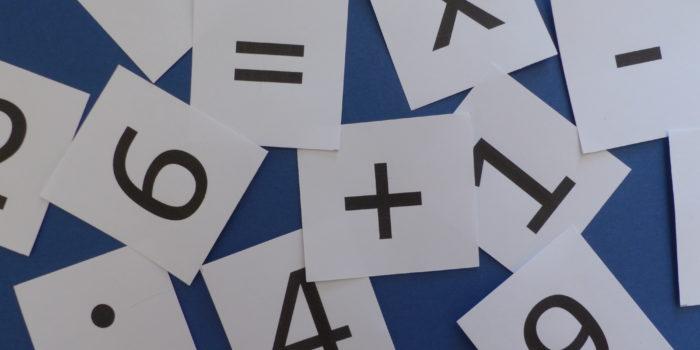 Kaartjes met cijfers en rekensymbolen liggen door elkaar als symbool voor het dyscalculie-programma van de Davis-methode.