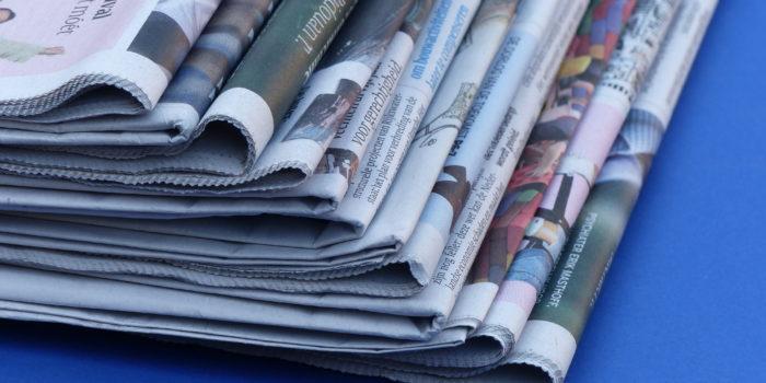 Een stapel kranten symboliseert de gemeenten en UWV waar Saisi opdrachten voor uitvoert.