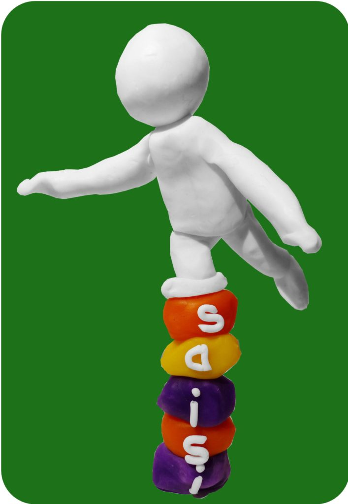 Dit klei-mannetje, dat balanceert op een stapeltje blokjes met Saisi er op, staat symbool voor het dyslexie-programma van de Davis-methode.